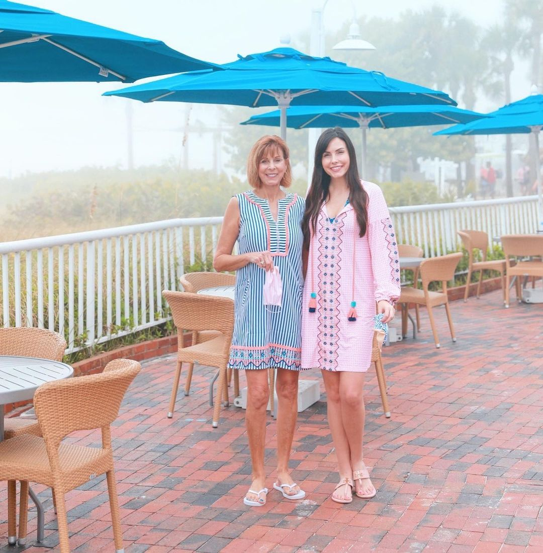 Two women standing in front of blue beach table umbrellas. Woman wearing Cabana Life St. Barts Tassel Cover Up and Woman wearing St. Barts Sleeveless Tunic Dress
