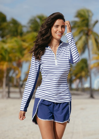 Woman walking in front of palm trees wearing Cabana Life Navy Stripe Sport Zip Polo