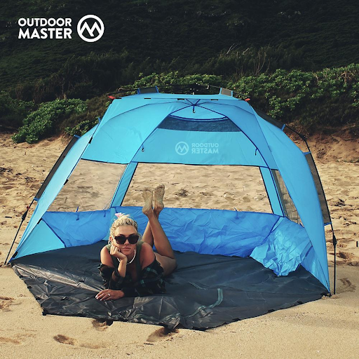 Woman laying in Outdoormaster Pop Up Beach Tent XL on beach