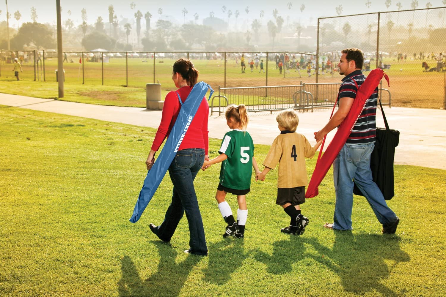 Family walking across grass at soccer game. Man and woman each carrying carrying a Sport-Brella XL over their shoulder