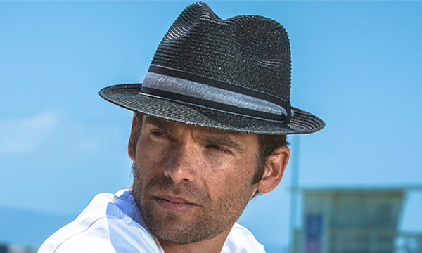 Man wearing a black hat by the beach