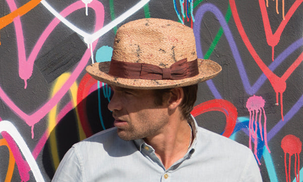 Man wearing a rust colored hat against a colorful graffitied wall