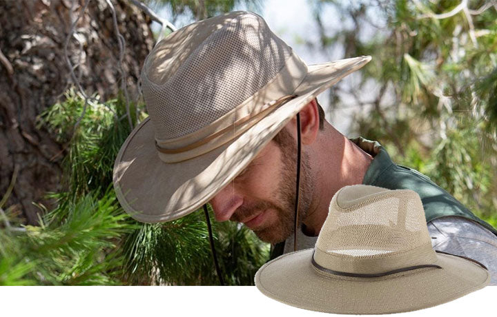 Man wearing a cream colored hat with straps near a tree