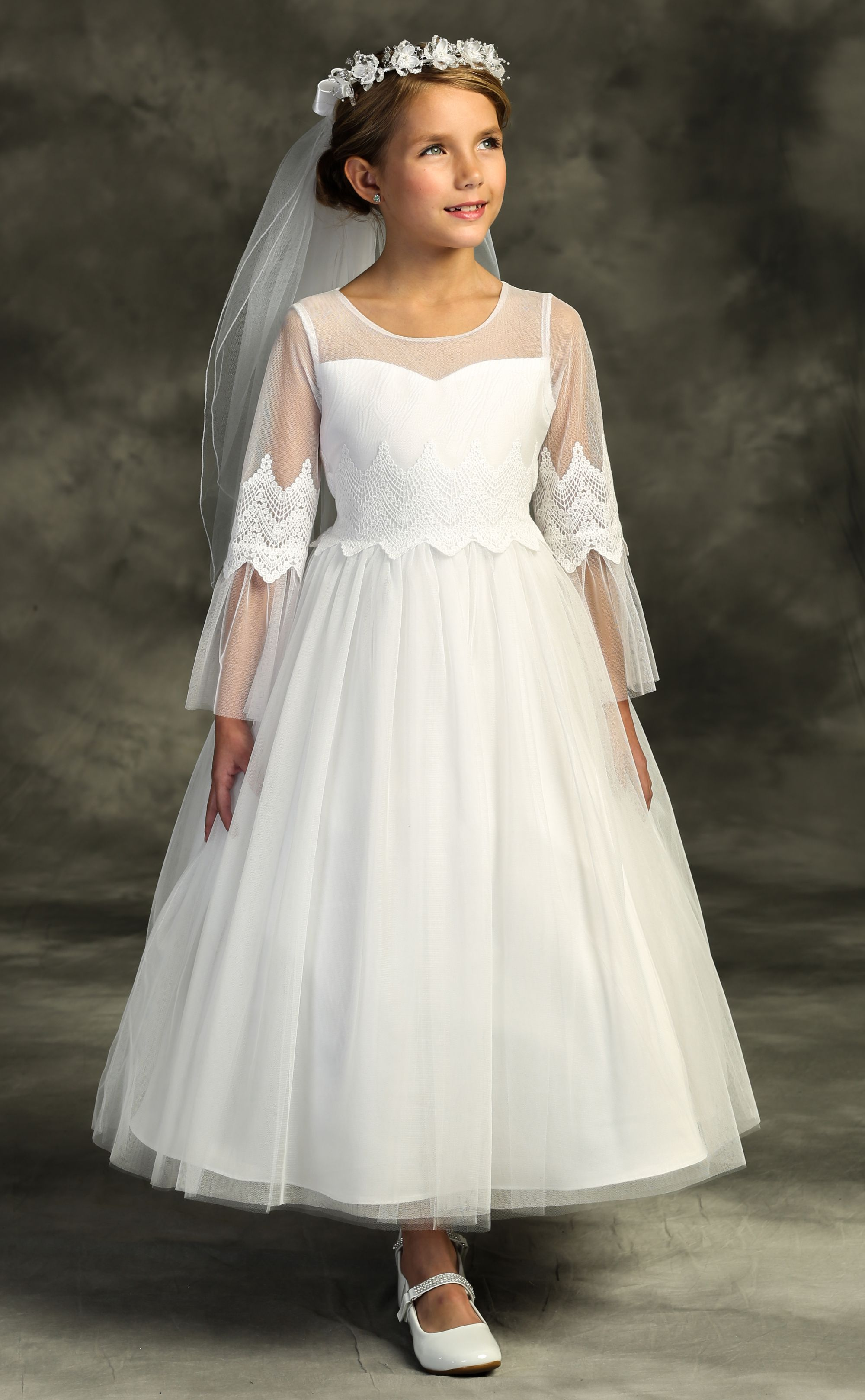 girl wearing white communion dress with veil