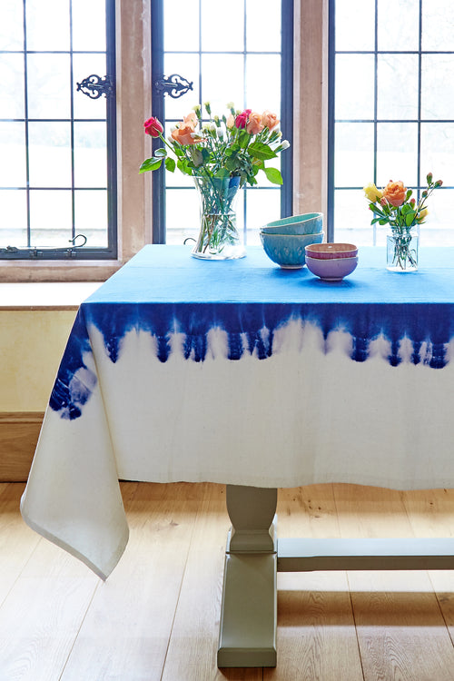 Lifestyle image of the tablecloth. Rich blue on the top, dip dyed down to the natural fabric.