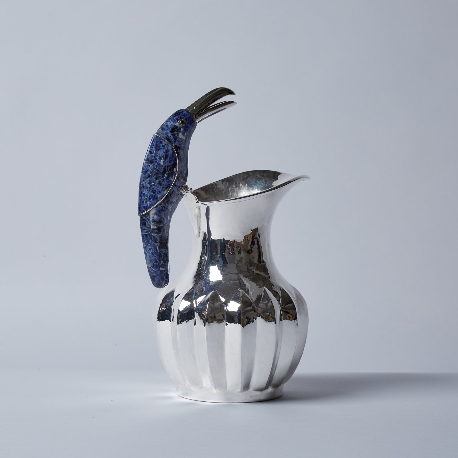A sprightly and curious bird, this blue lapis toucan is the perfect finishing touch to the uniquely shaped silver jug.