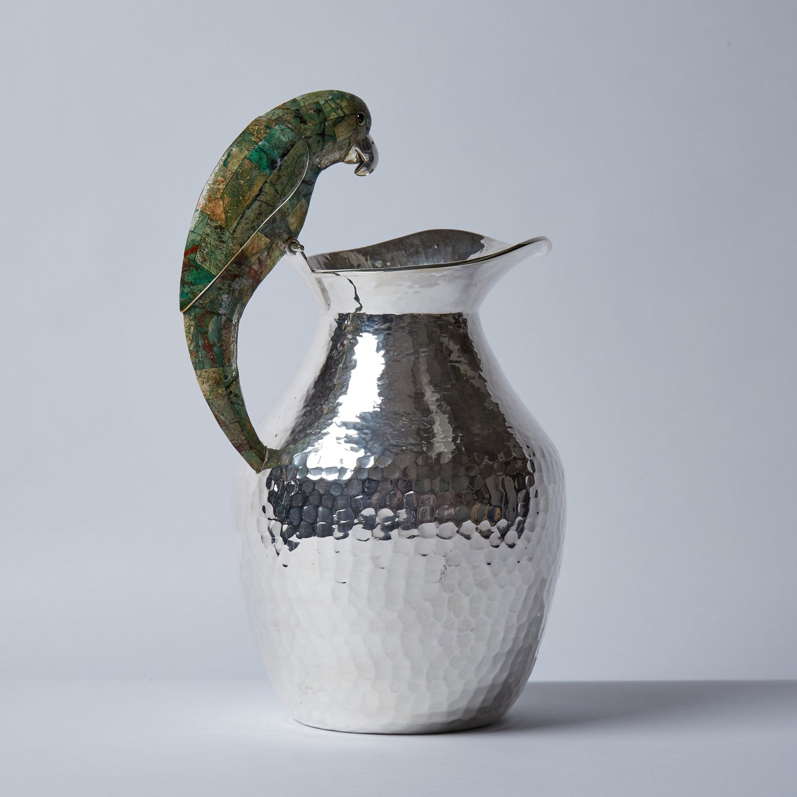 A peacefully perching parrot, mosaicked in malachite stone, with it's tong curved bill and beady eyes, enriches this splendid jug.