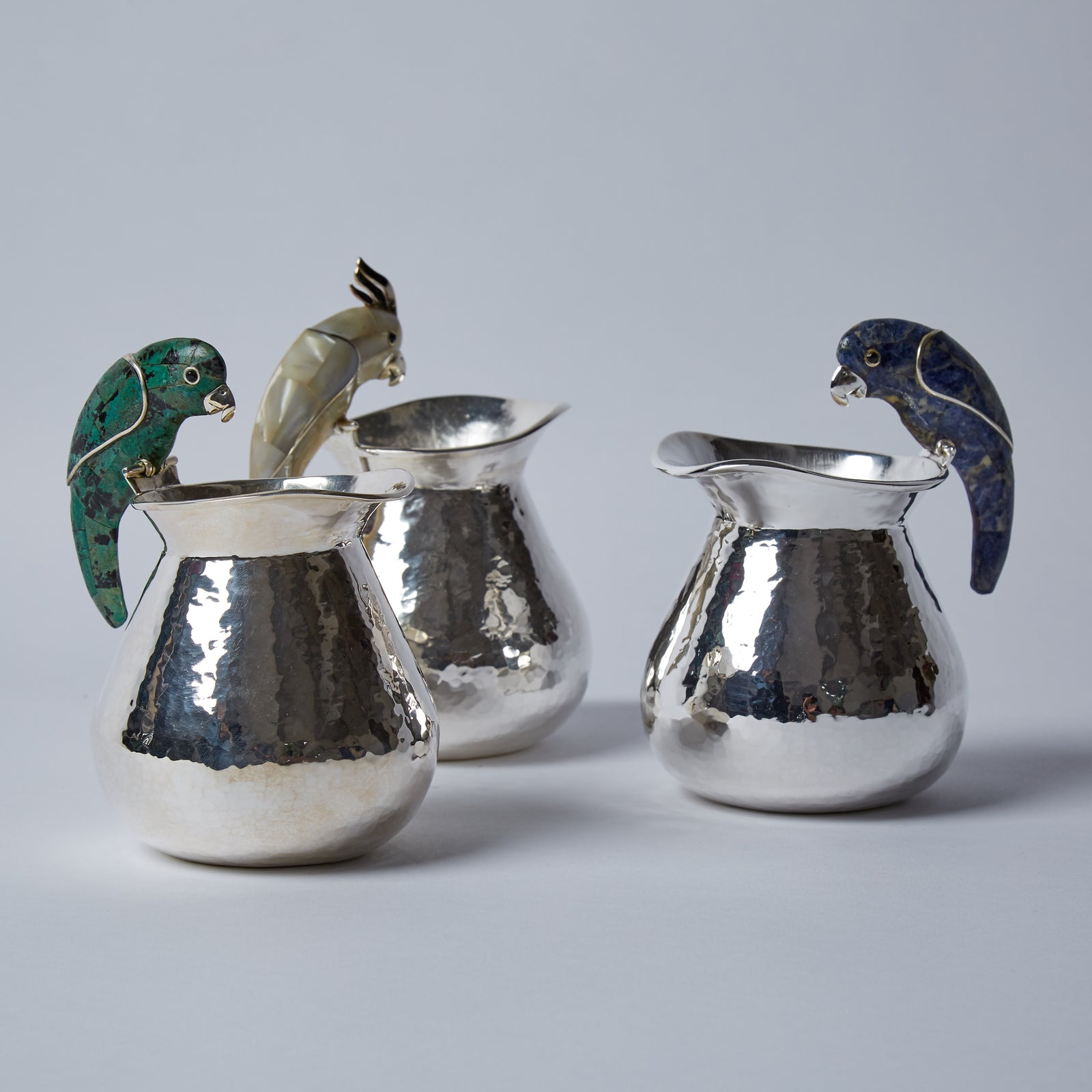 A collection of cremera jugs, adorned with a flock of mosaicked birds