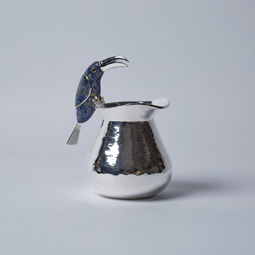 This nosey little fellow, perching on the edge of the jug, is keeping a look out over your table.