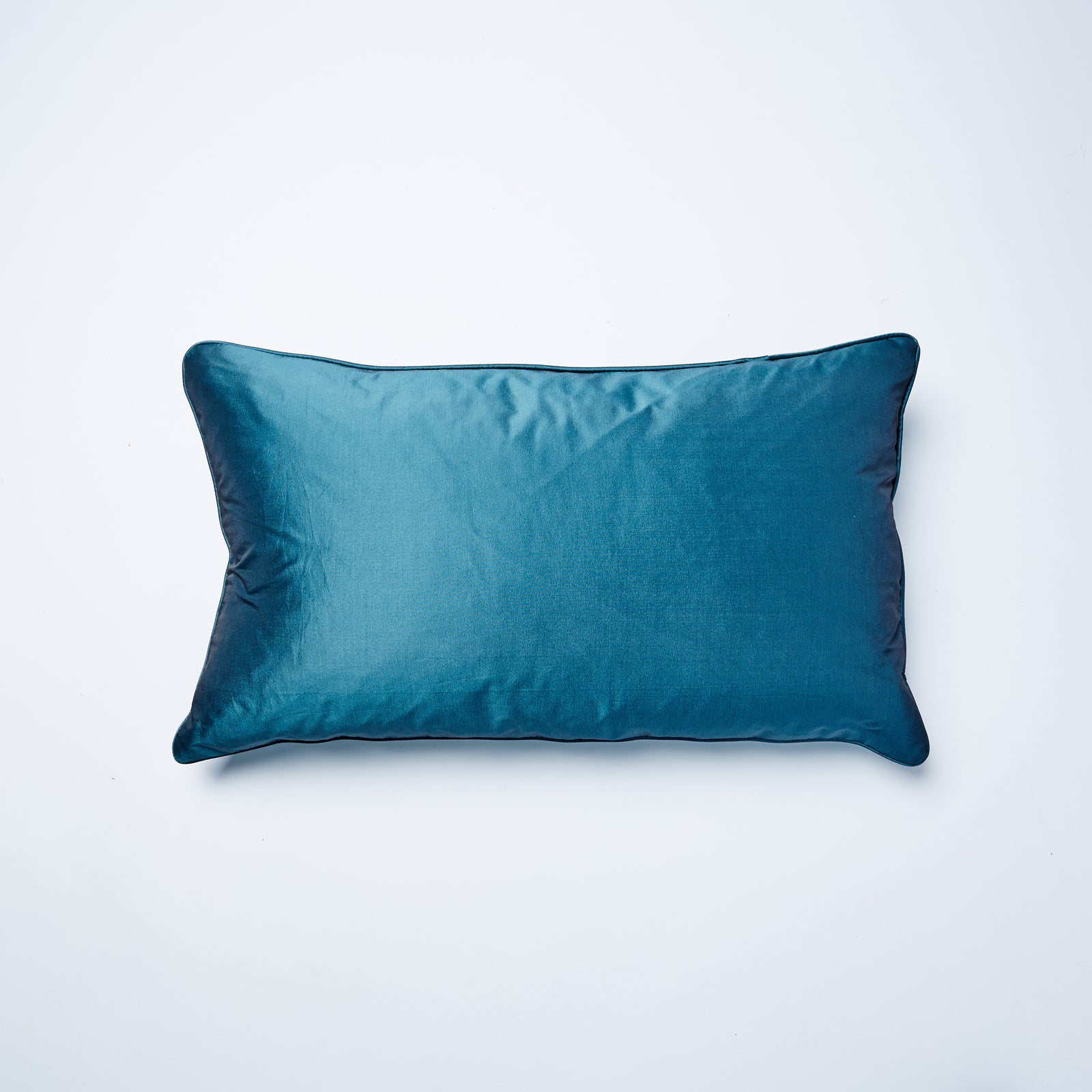 A rich turquoise hue covers the back, perfect completing the handiwork decorating the cushion's front