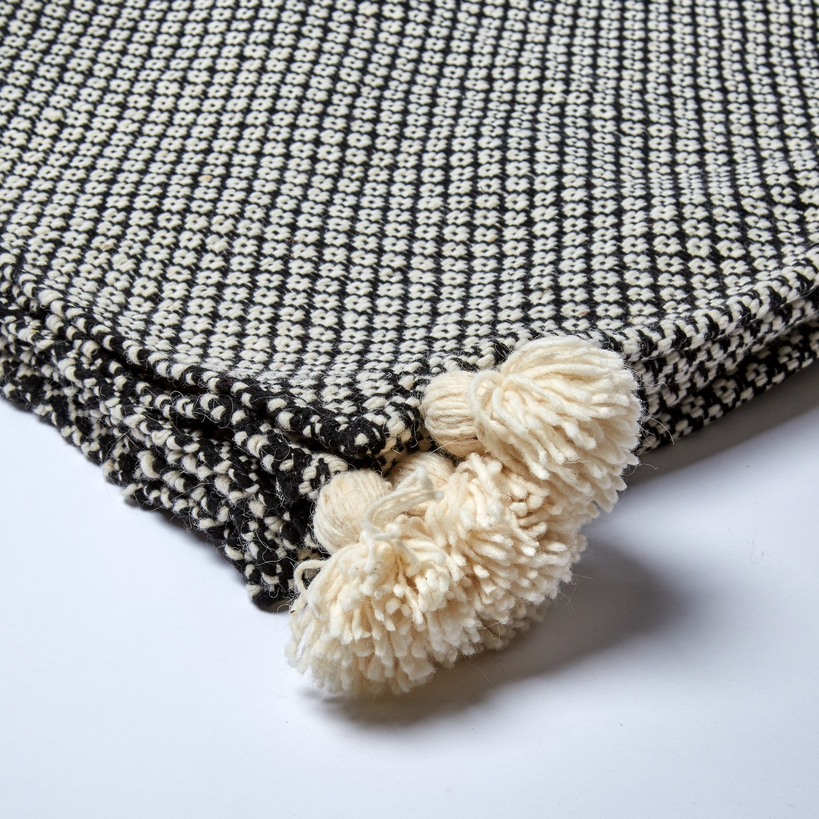 Handwoven in the Atlas Mountains in luscious wool, this accessory is perfectly completed by the oversized, exuberant pom poms which run along the edges.