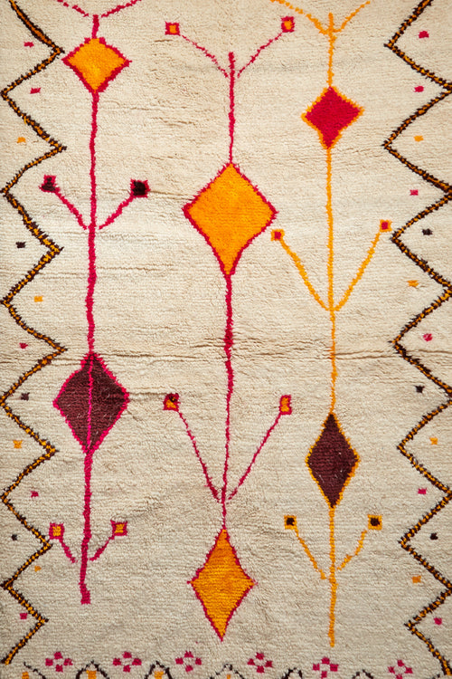 A variation on the traditional Ben Ourain rug. Rich yellows, pinks, browns and oranges stand out against the natural background.