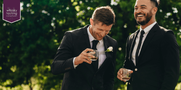 Groom and best man drinking whisky from best man gift
