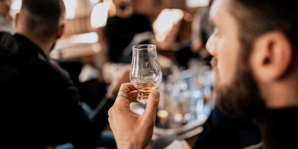 man tasting whisky with his friends