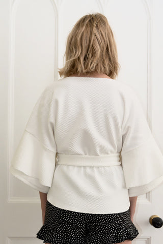 White Textured Cape With Waist Tie & Frill Sleeves by Minkie London on OOSTOR.com