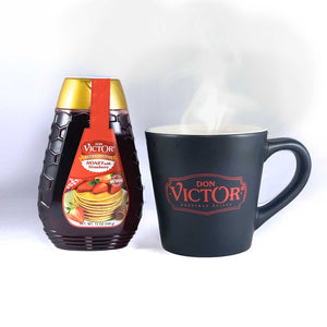 Bottle of Don Victor natural strawberry flavored honey beside a steaming mug of hot honey tea.
