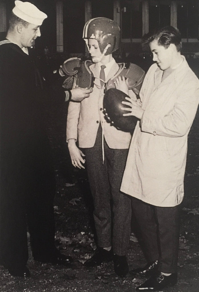 David Bowie trying on American Football gear with his friend George Underwood, both wearing Denson Winklepickers in autumn 1960