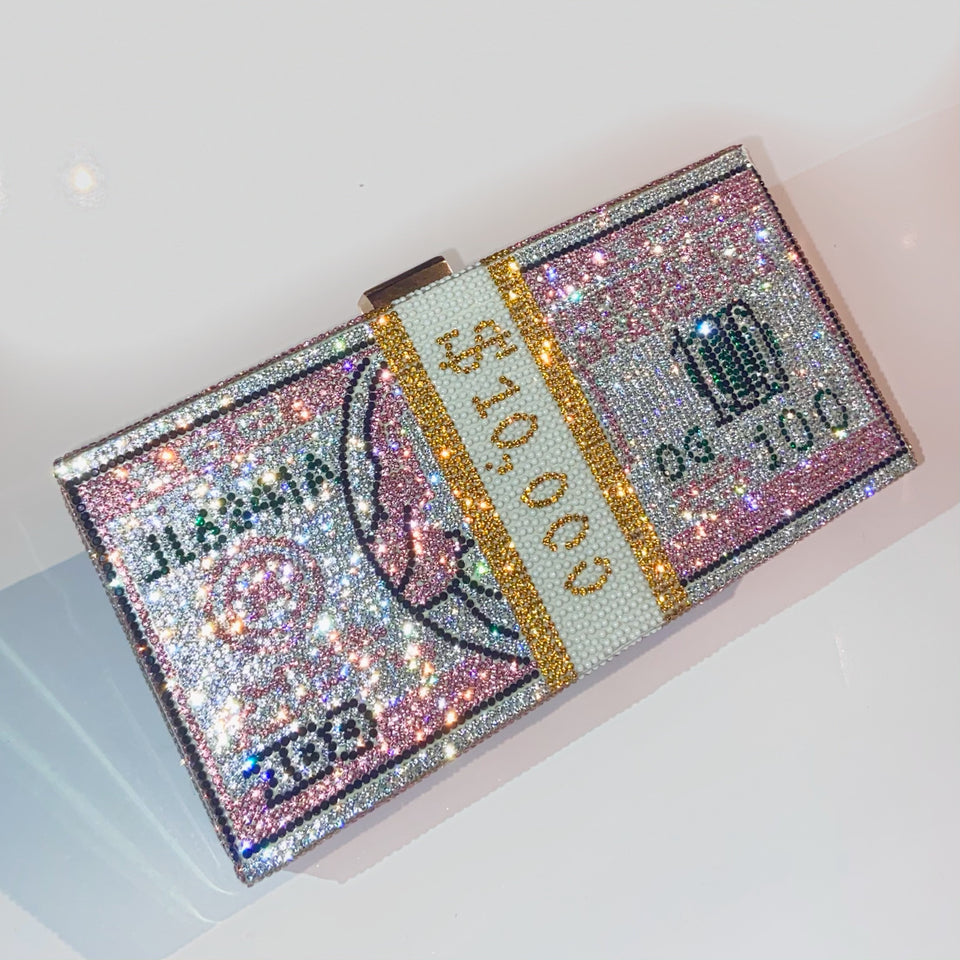 "sparkly pink clutch sized 10,000 bill. displaying ""shop accessories"" collection"