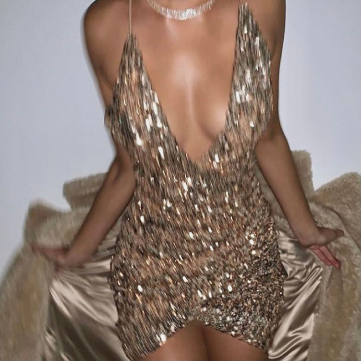 "model in a sparkly tan dress holding a tan coat. displaying ""shop dresses"" collection"