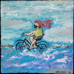 Masked Red Headed Women Pedaling a Bike on Beach by Mark San Souci
