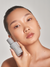 Asian female holding EVENPRIME Barrier Serum