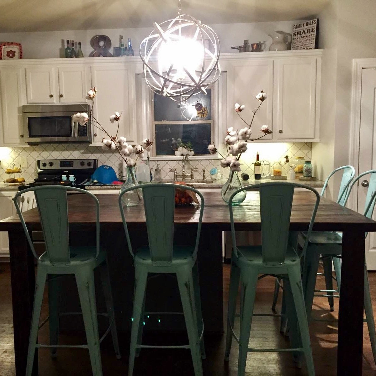 Coffee colored kitchen island and bar with turquoise barstools