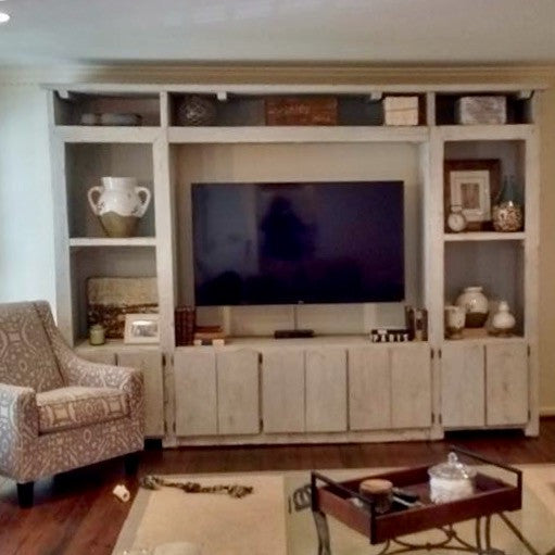 White distressed wood shelving and entertainment center with space for large tv and decorations. Covered and open shelf space
