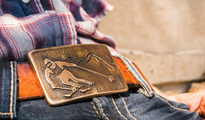 Bronze belt buckle featuring a skier ripping a sick turn