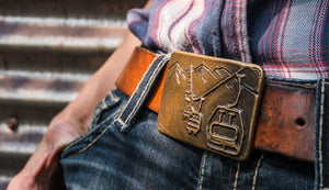 Bronze belt buckle features a ski life line