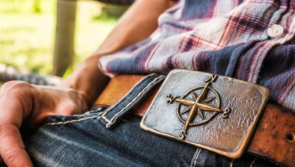 A compass is the featured item of this bronze belt buckle
