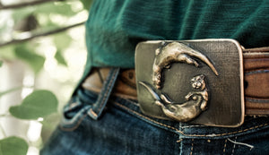 An amazing adaptation of river otters on a bronze belt buckle