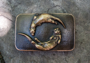 Mountain Gypsy Studios released this bronze belt buckle of two river otters playing