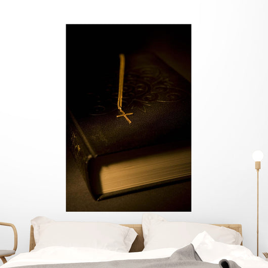 Gold Cross Pendant Resting On A Book Wall Mural