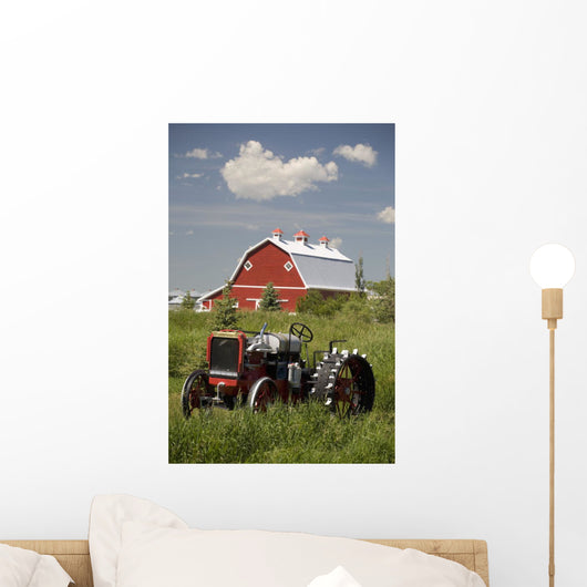 Old Red Tractor In A Field With A Red Barn In The Background Wall Mural