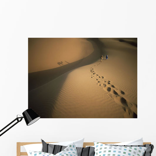 Man's Lonely Travel through the Desert with Trusted Camel Companion Wall Mural