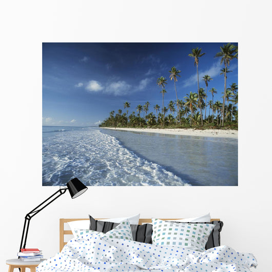 Waves Lapping Shore Of Beach With Palm Trees Behind Wall Mural