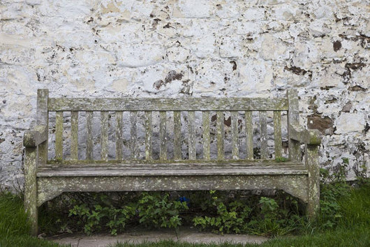 A Wooden Bench With Peeling Paint Against A White Wall Wall Mural
