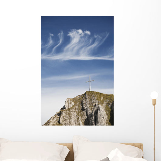 Mountain Peak With A Cross On Top Against A Blue Sky With Clouds Wall Mural