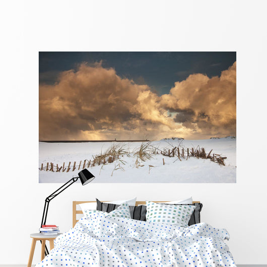 Illuminated Clouds Glowing Above A Snowy Field Wall Mural