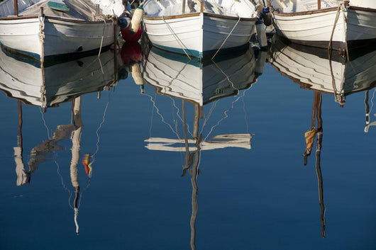 Boats mooring in a harbour with the mirror image in the tranquil water Wall Mural