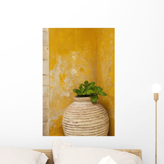 Vase holding a plant against a yellow wall Wall Mural