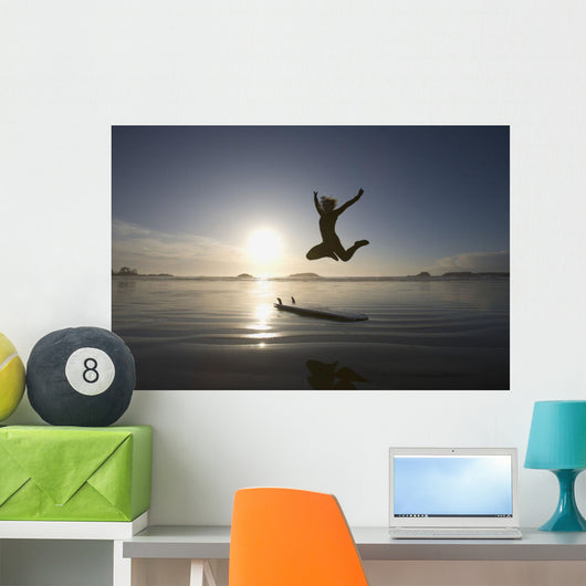 Silhouette Of Female Surfer Jumping For Joy Wall Mural