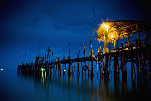 Lights On A Wooden Pier Leading Out In The Water At Night Wall Mural