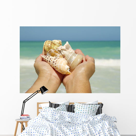 Hawaii, Woman's Hands Holding Seashells, Ocean In Background Wall Mural