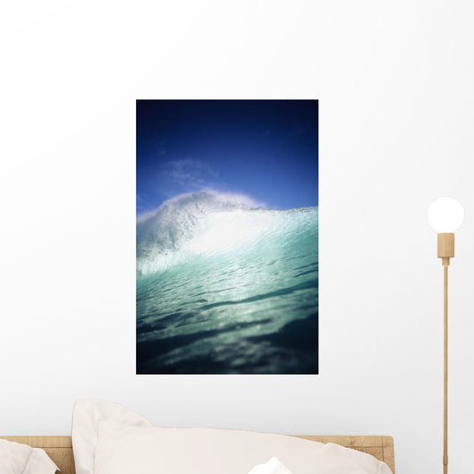 Closeup angle of green wave with backlit crest, bright blue sky Wall Mural