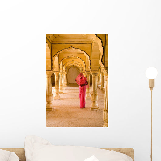 Woman In Bright Pink Sari Stands Beneath Arches Wall Mural