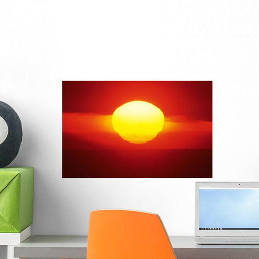 Gorgeous Sun Setting In Bright Orange Sky Over Ocean Wall Mural