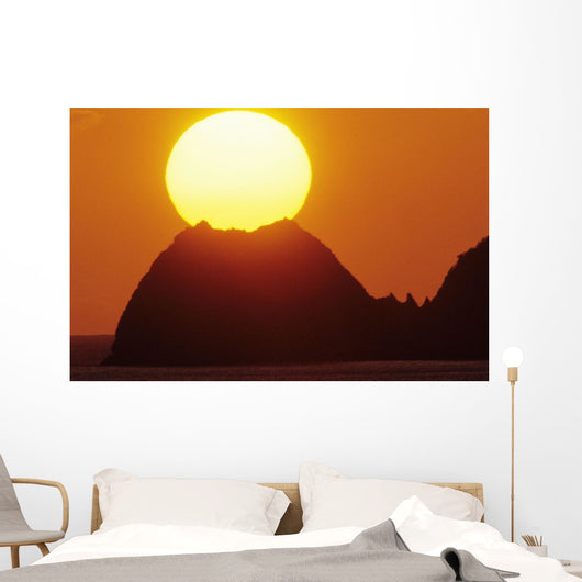 Sun Setting In Orange Sky Over Ocean And Silhouetted Hill Wall Mural