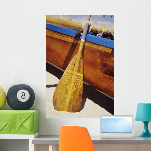 Wooden paddle and outrigger canoe on beach Wall Mural
