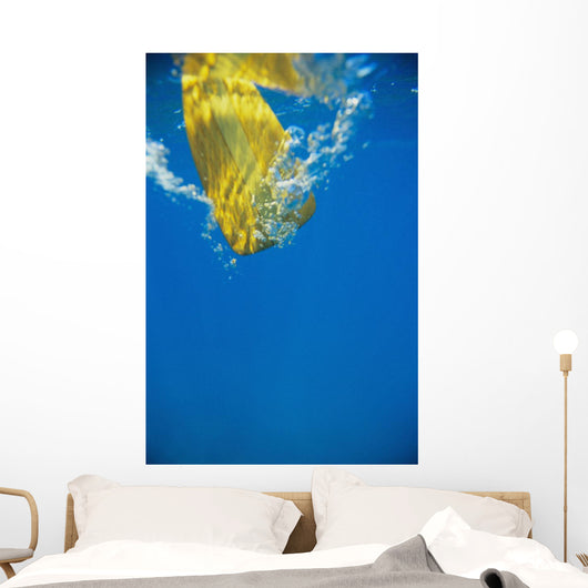 Underwater View Of Yellow Paddle Stroking Water, Creating Bubbles Wall Mural